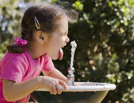 little girl drinking from water fountain