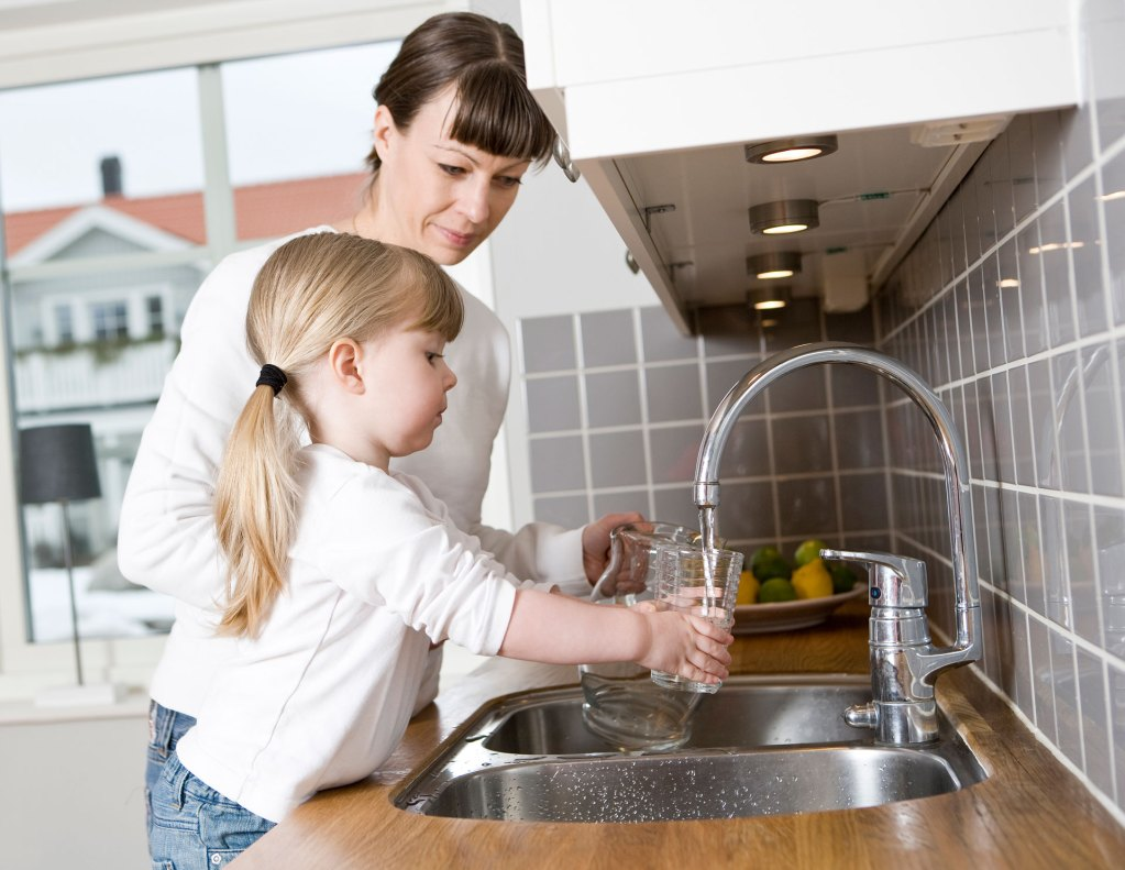Mother and daughter drinking clean tap water