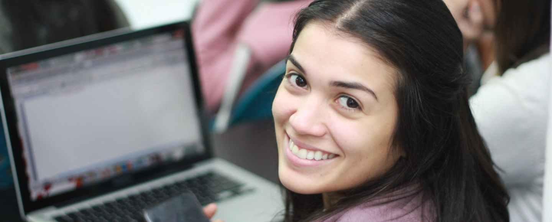 smiling woman in pink blazer using macbook pro