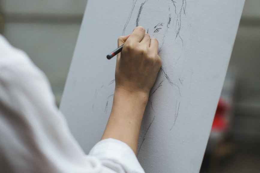 woman in white long sleeve shirt drawing on paper