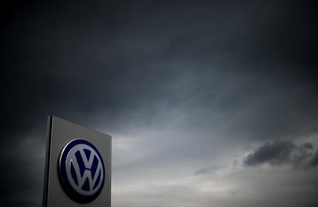 The logo of German car maker Volkswagen can be seen as dark clouds hang in the sky over a Volkswagen trader in Hanover, central Germany, on September 22, 2015. Share prices on the Frankfurt stock exchange fell more than 3.0 percent in midday trading on September 22, 2015, pushed down by index heavyweight Volkswagen, as it ploughed ever deeper into a pollution cheating scandal. AFP PHOTO / ODD ANDERSEN