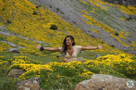 Gaby abre los brazos rodeada de flores, en un paisaje de montaña en los Pirineos de Huesca