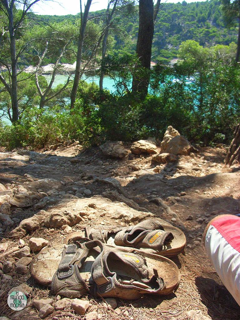 Sandalias de montaña mimetizadas con la tierra de una playa de menorca