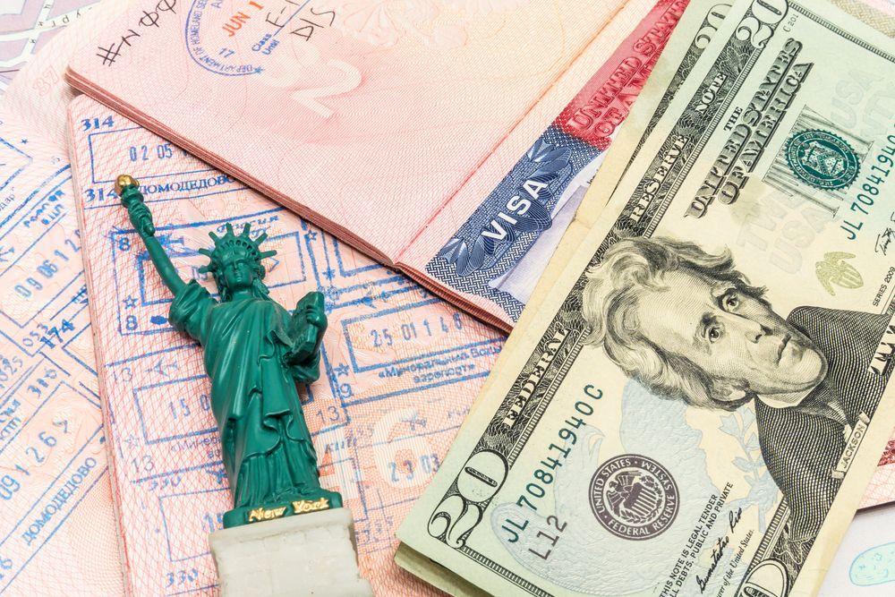 Pasaporte con sello y visa americana, pequeña estatua de la libertad y moneda oficial de los EE.UU.