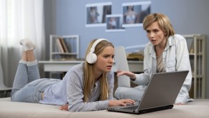 Teenager in headphones ignoring mother, surfing net, difficult puberty age