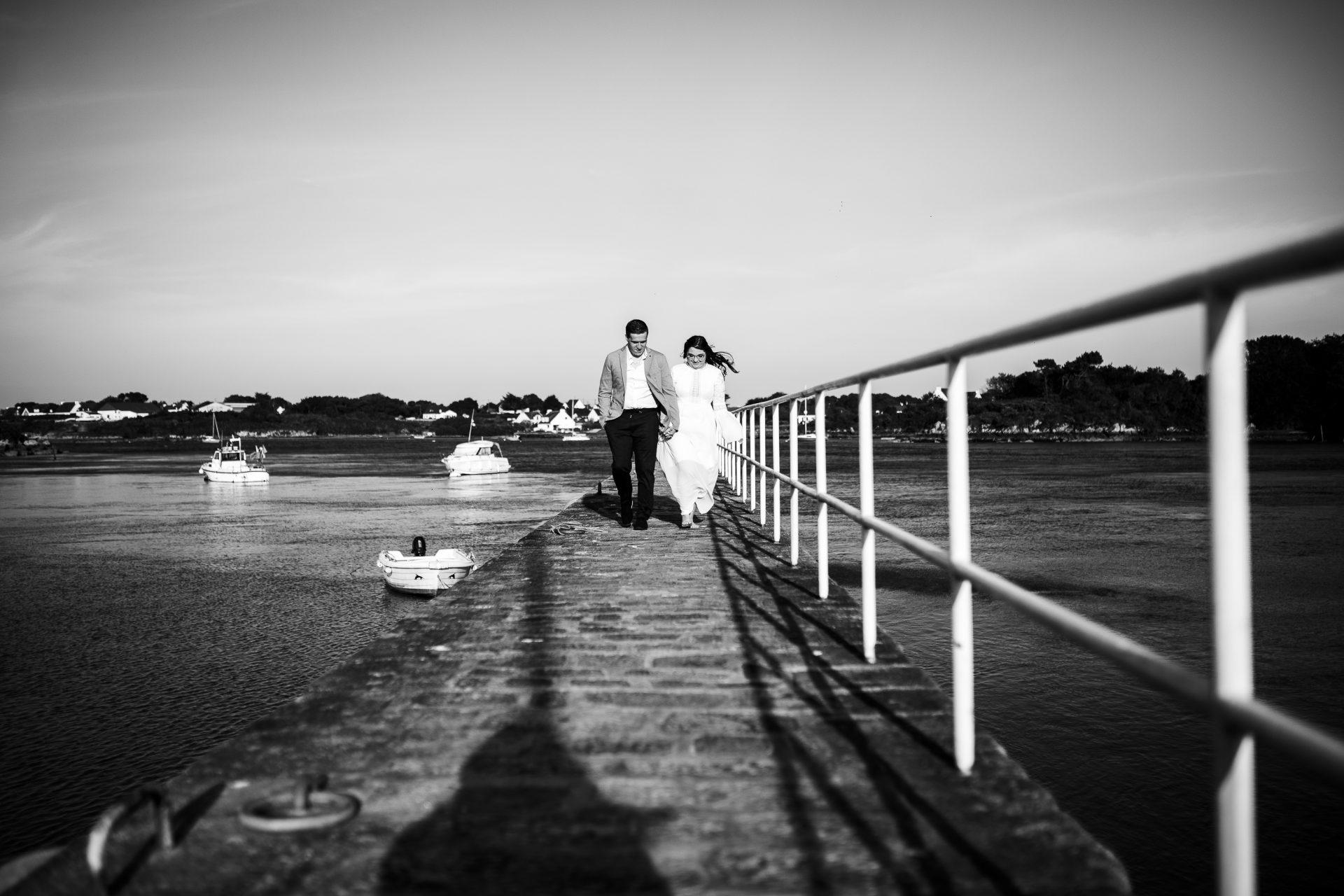 couple de futurs mariés qui marchent sur la digue à Plouhinec.