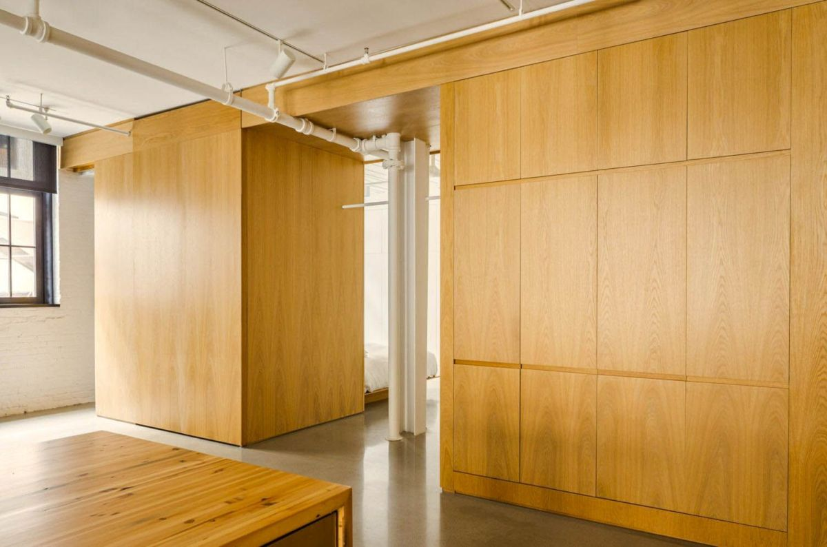 Wood accent as partition and cabinetry in MCGILL 120 renovation for a loft in Vieux Montreal (1)