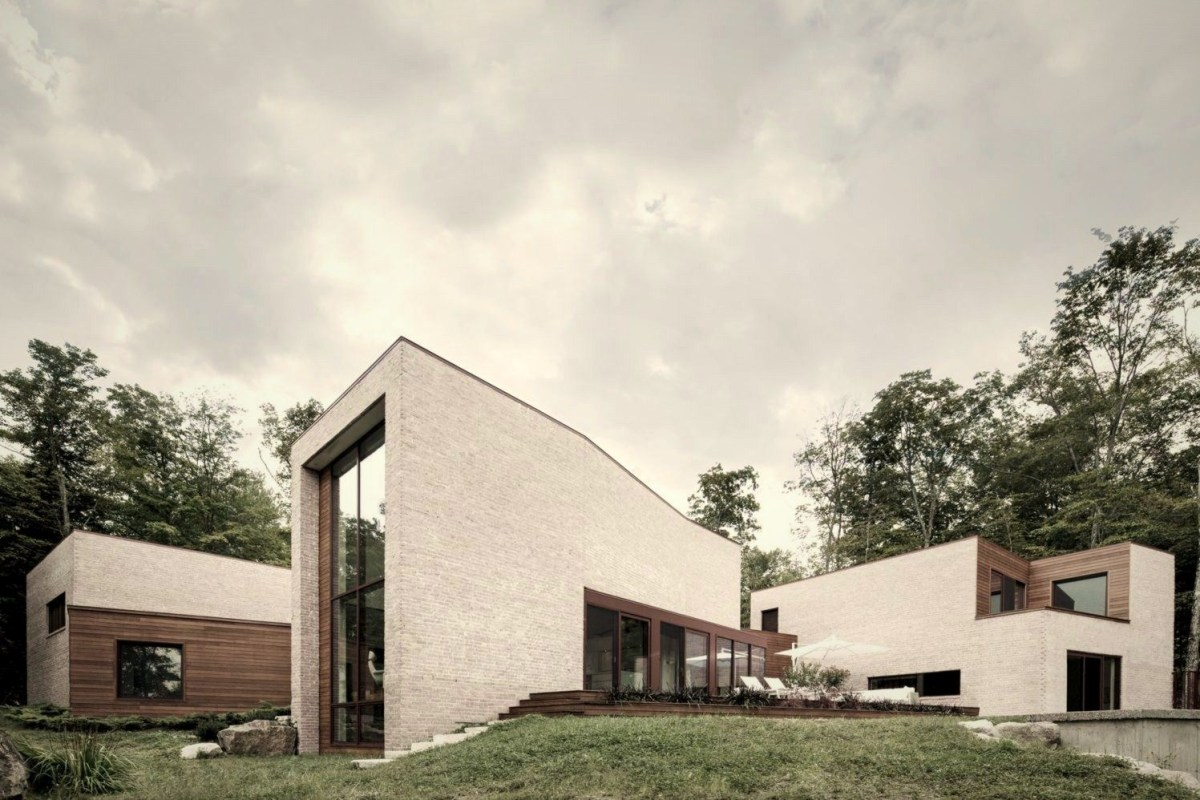 Futurist house design Les Elves in Quebec with box house style and lots of large windows build on sloping land (3)
