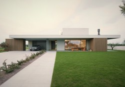 Impressive architecture work underscoring flat roof house style in the middle of green grass field