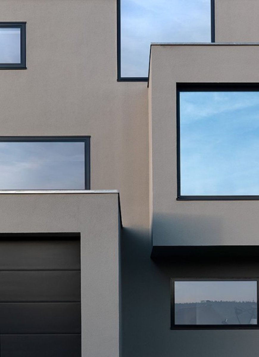 Neoteric facade design of House F presenting jutted out windows and garrage doors (3)