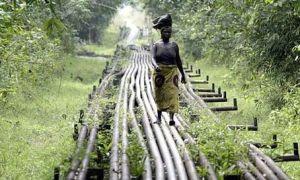 Un mujer camina sobre tuberías que transportan gas desde un yacimiento explotado por petroleras británicas.