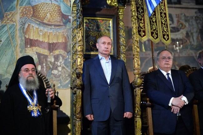 Putin flanqueado por el protos y el Ministro Griego de Asuntos Exteriores durante un servicio religioso en Karyes. Imagen: Alexei Druzhinin. Daily Mail