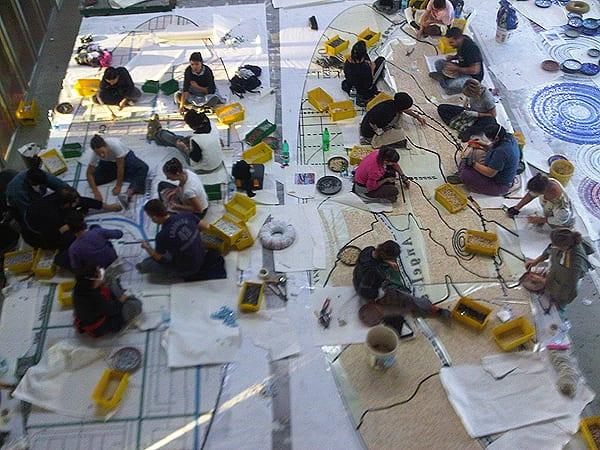 Equipos de artesanos de SICIS arman la obra de arte de mosaicos diseñados para la estación Sherman Way.