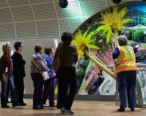 Una guía de Metro da una explicación sobre el mural de cerámica Kaleidoscope Dreams, de la artista Anne Marie Karlsen. La obra es acerca de los sueños y aspiraciones de los inmigrantes de San Fernando Valley