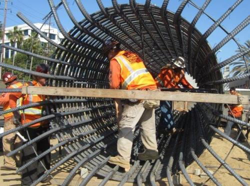 Trabajadores de la construcción trabajan en la armazon de lo que será una columna para el puente en Olympic Boulevard.