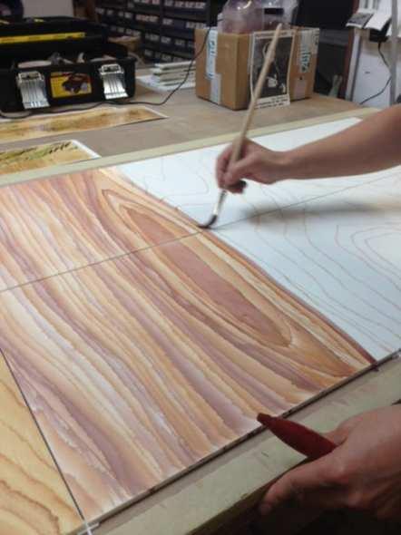 Artesanos pintan cuidadosamente un panel de madera. Foto: Mayer of Munich.