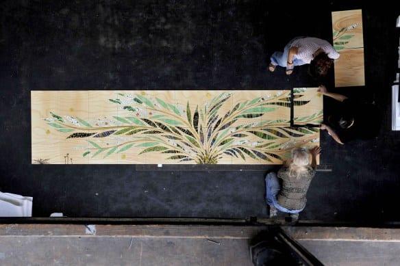 Artesanos colocan los mosaicos en las losetas de cerámica.