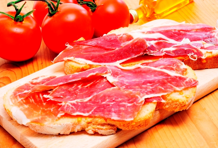 sliced of bread with serrano ham served as tapas