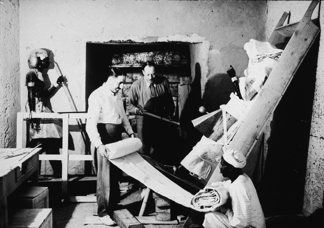 British archaeologists Howard Carter (1874 - 1939) (left) and Arthur Callender (died 1937) carry out the systematic removal of objects from the antechamber of the tomb of Pharaoh Tutankhamen, better known as King Tut, with the assistance of an Egyptian laborer, Valley of the Kings, Thebes, Egypt, 1923. (Photo by Hulton Archive/Getty Images)