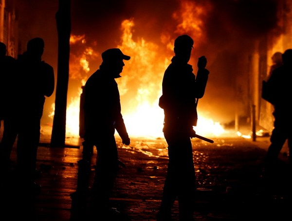 Spanish National police officers stand in front of burning garbage bins during clashes after a street hawker died in central Madrid, Spain, March 15, 2018. REUTERS/Stringer     NO RESALES. NO ARCHIVE.