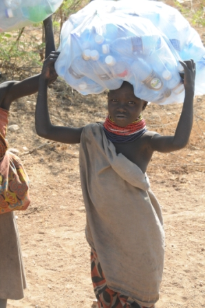 Lokichoggio - Turkana boy collecting plastic bottles