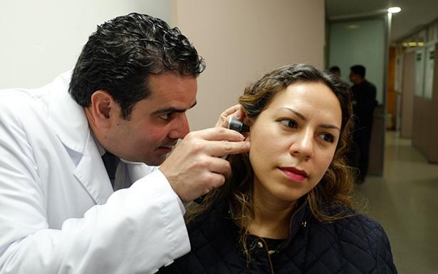 Médico del IMSS revisando los oídos