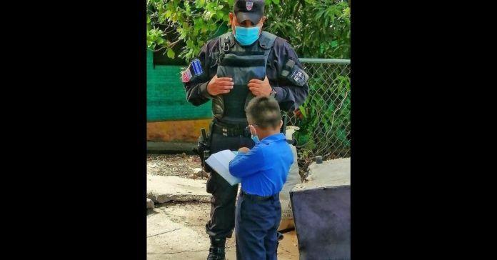 Se hace viral la fotografía de un pequeño predicando la palabra de Dios a un elemento de la PNC que lo escucha con mucha atención