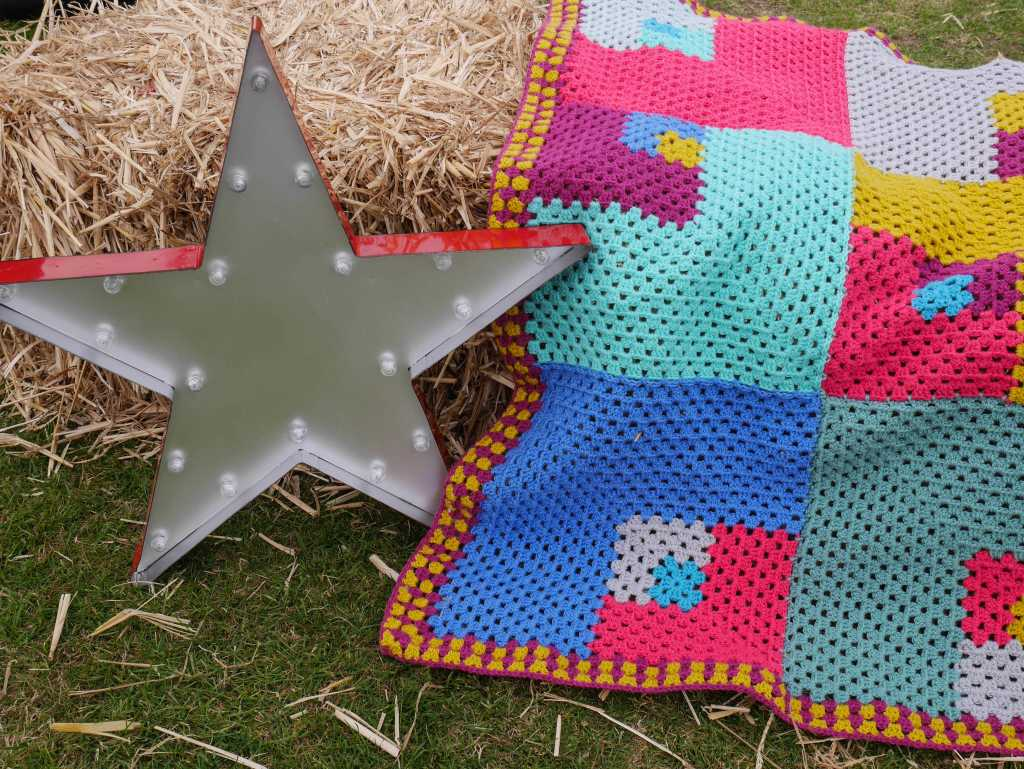 Unpredictable Granny crochet blanket on a hay bale
