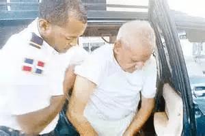 Un agente de seguridad de la cárcel de Rafey ayuda al empresario y presidiario Adriano Román a salir de una jeepeta para internarlo.