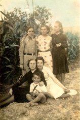 """El petit Isidro del """"Francisquet"""", davant la seva tieta Ramona, que té al costat la Maria Pelegrí, novia del després beatificat Francesc Castelló. Dretes, la Carme, la Inés i la Ramona de cal """"Carreter""""."""