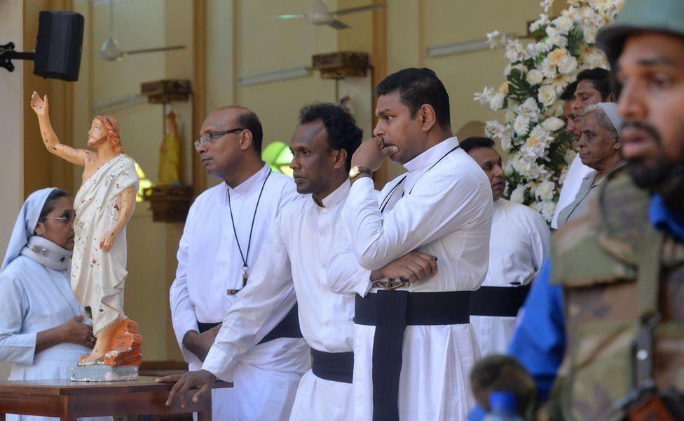 Sacerdotes católicos dentro de la iglesia de San Sebastián en Katuwapitiya, Negombo, junto a una estatua de Jesucristo salpicada de sangre. Foto cortesía