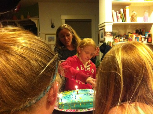 She made the cake herself, now lights it watched by sisters and Mum