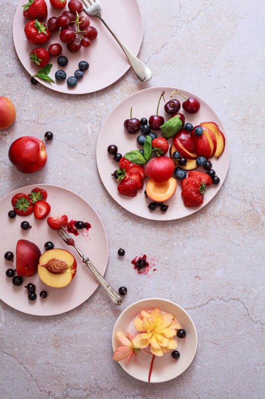 Fresh summer fruits on pink plates