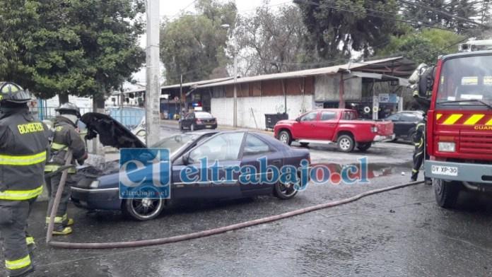 Personal de Bomberos de San Felipe tirando agua al motor para enfriarlo.