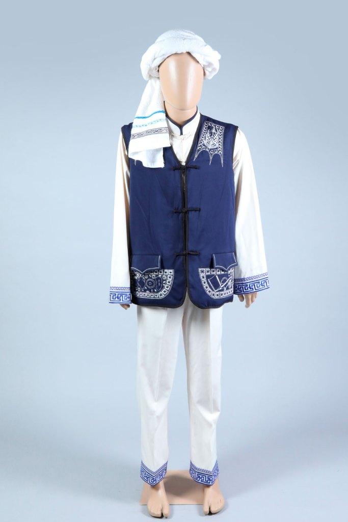 Chaleco sobre casaca de manga larga y pantalón bordados con turbante en la cabeza.