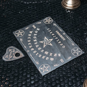 A quaint looking Ouija Board and planchette.