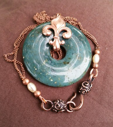 moss agate donut with red bronze fleur-de-lis, and copper chain with preciosa seed beads