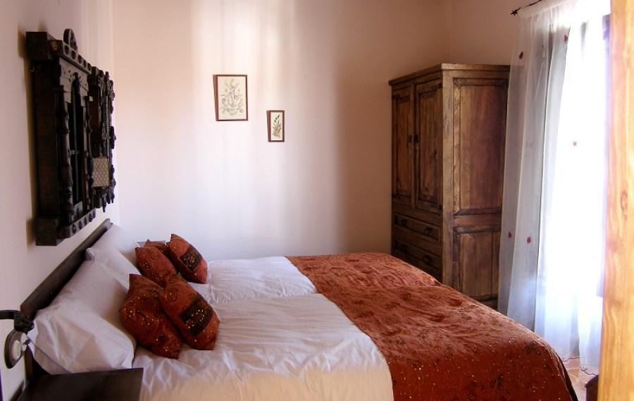 Un dormitorio de dos camas bañado por una inmensa luz natural