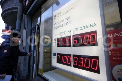 A digital display shows the latest U.S. dollar and euro foreign currency exchange rate outside a Bank Saint-Petersburg bank branch in Saint Petersburg, Russia, on Thursday, Dec. 18, 2014. President Vladimir Putin struck an uncompromising stance over the crisis gripping Russia, accusing the U.S. and European Union of trying to undermine his nation and blaming external factors for the ruble's sharp drop. Photographer: Andrey Rudakov/Bloomberg