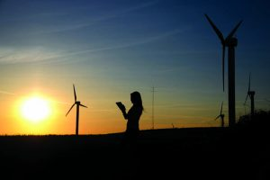 climate justice. Photo by Richard Dacker from Pexels https://www.pexels.com/photo/silhouette-of-woman-holding-book-near-windmills-636335/