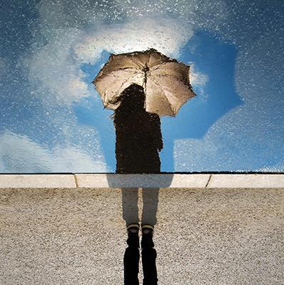 Reflection of a girl holding an umbrella
