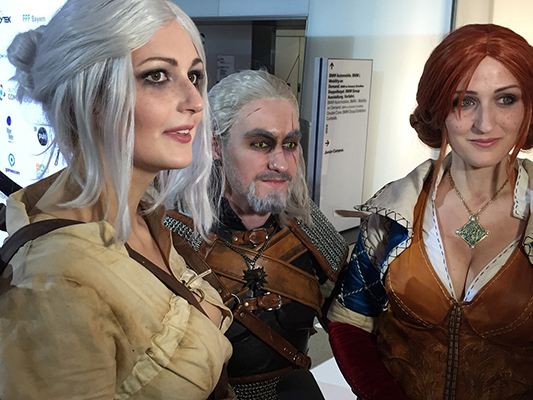 A man and two women dressed in Witcher-themed costumes