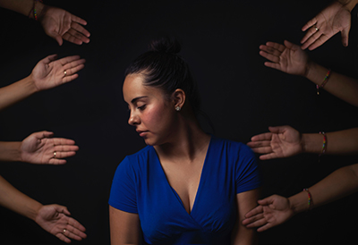 Woman surrounded by reaching hands