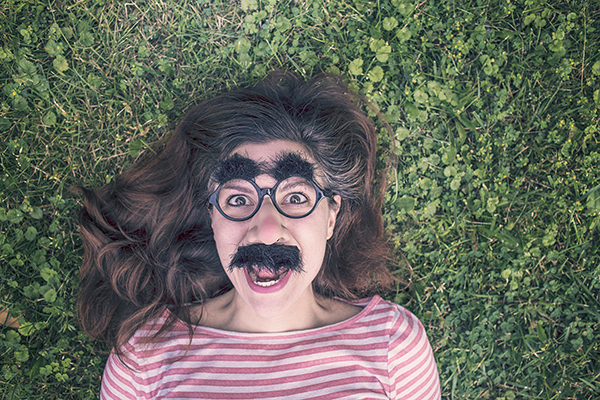 girl lying in grass with mustache and glasses