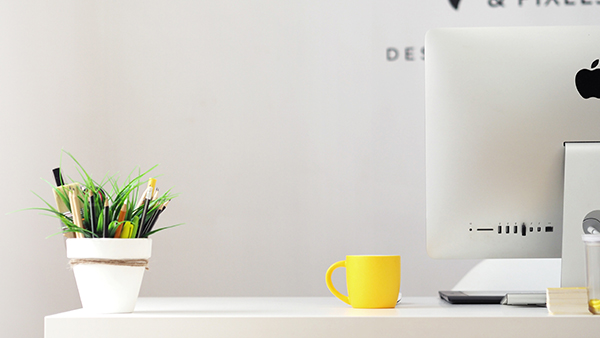 computer on white desk with plant and yellow mug