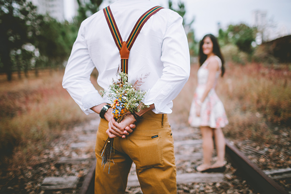 man holding bouquet of flowers behind his back
