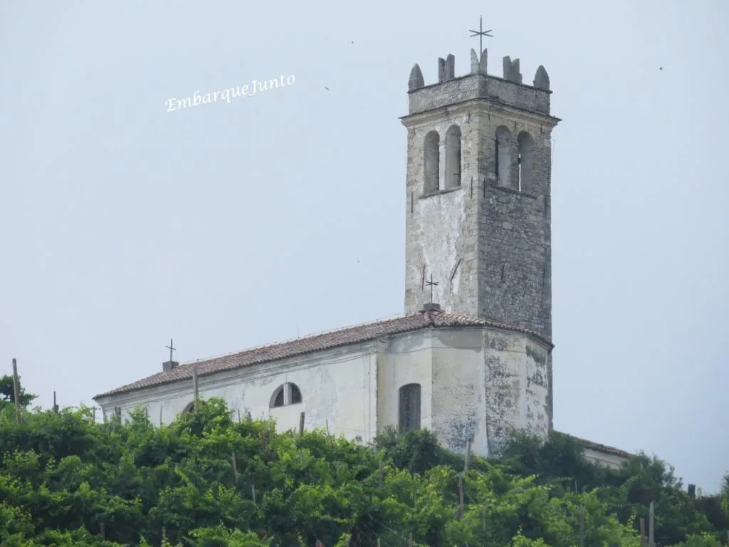 Capela de São Lourenço com uma torre sineira com telhado com ameias de cauda de andorinha (lado norte).