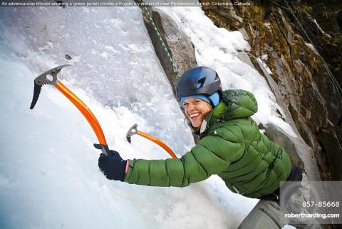 An adventurous female wearing a green jacket climbs a frozen icy waterfall near Pemberton, British Columbia, Canada.