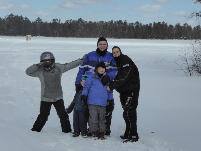 Family Picture in Snowmobile Gear on Frozen Lake - Outside the Comfort Zone