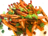 Baked paprika-sprinkled sweet potato fries with parsley and pomegranate